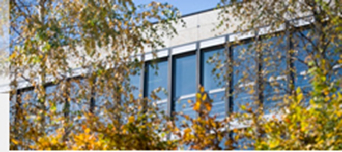 View of the glazed facade of the university's Library Building surrounded by an autumnal landscape.